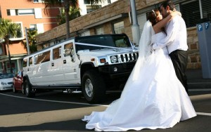 Bride and groom posing infront of white wedding hummer limousine in connecticut photo